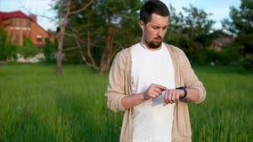 Een mens controleert op een slim horloge hoeveel kilometers hij in het park in de zomer in werking stelde stock videobeelden