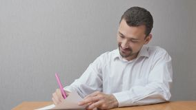 Een mens creeert een hart op papier en glimlacht gelukkig stock afbeelding
