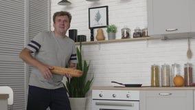 Een mens danst en zingt in de ochtend in de keuken met een brood van wit pluksel stock video