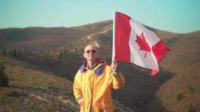 Een mens in de bergen bevindt zich en houdt de Canadese vlag Hij draagt heldere gele kleren en glazen stock footage