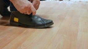 Een mens in de dienst bindende schoenveters op schoenen stock video