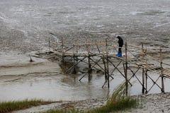 Een mens in de getijde vlakke rivierbrug bij de visserij stock fotografie
