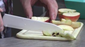 Een mens in de keuken die een appel snijden stock video