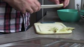 Een mens in de keuken die een appel snijden stock footage