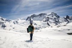 Een mens in de laag van de camouflagewinter en rugzak die zich voor de achtergrond van sneeuwberg bevinden Stock Fotografie
