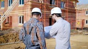 Een mens de voorman en de gebaarde klant bespreekt het plan voor de bouw van een nieuw buitenhuis in a stock video