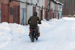 Een mens in de winterkleren die een motorfiets berijden op een sneeuwweg royalty-vrije stock foto's