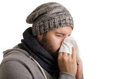 Een mens in de wintertijd met ziekte moet in een zakdoek niezen en blazen die op witte achtergrond wordt geïsoleerd stock foto