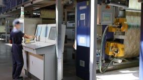 Een mens dichtbij het controlebord van een transportbandlijn voor de productie van behang, een transportband voor de productie va stock videobeelden