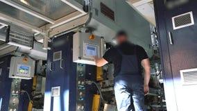 Een mens dichtbij het controlebord van een transportbandlijn voor de productie van behang, een transportband voor de productie va stock video