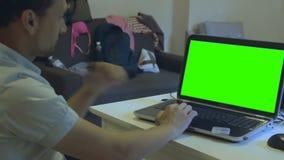 Een mens die aan chromakeylaptop werken in een ruimte met knoeit stock video