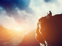 Een mens die aan laptop op de piek van een berg werken stock foto's