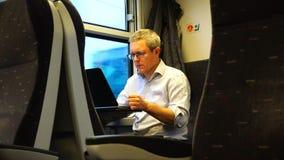 Een mens die aan laptop op de trein werken stock video