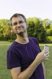 Een mens die aan muziek op zijn smartphone luisteren Stock Fotografie