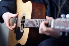 Een mens die akoestische houten zes-koord gitaar spelen stock foto