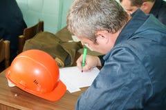 Een mens die als ingenieur met een oranjegele helm aan de lijst werken is het bestuderen, schrijvend in een notitieboekje bij een stock foto's