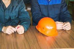 Een mens die als ingenieur met een oranjegele helm aan de lijst werken is het bestuderen, schrijvend in een notitieboekje bij een stock afbeelding
