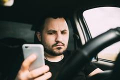 Een mens die die een auto drijven door een smartphone wordt afgeleid royalty-vrije stock fotografie
