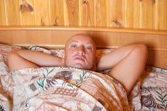 Een mens die die in bed liggen met een deken wordt behandeld royalty-vrije stock foto's