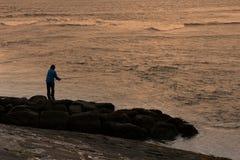 Een mens die bij zonsondergang vissen Royalty-vrije Stock Afbeelding