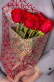 Een mens die een boeket van rode rozen houden stock afbeelding