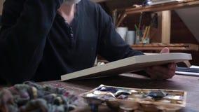 Een mens die een canva voor tekening nemen stock videobeelden