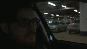 Een mens die de auto drijven bij undergroungparkeren Sluit omhoog De achtergrond van Bokeh stock footage