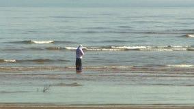 Een mens die in de golven zich voor de kust bevinden, visserij stock videobeelden