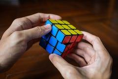 Een mens die de kubus van Rubik oplossen stock afbeeldingen
