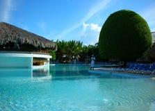 Een mens die de pool schoonmaakt bij tropische toevlucht Stock Foto