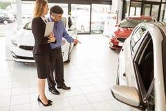 Een mens die een auto tonen aan de verkoopster Royalty-vrije Stock Fotografie