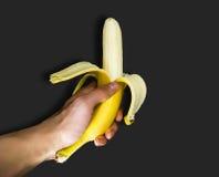 Een mens die een banaan in hand houden Stock Afbeeldingen
