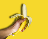 Een mens die een banaan in hand houden Stock Fotografie