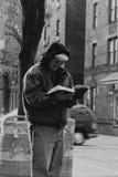Een mens die een boek buiten de Queensbibliotheek lezen in Jackson Heights Stock Foto