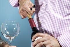 Een mens die een fles rode wijn ontkurken Royalty-vrije Stock Foto