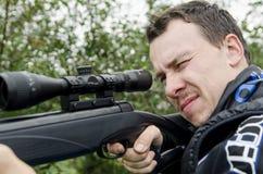 Een mens die een geweer houden en neemt doel Stock Afbeeldingen