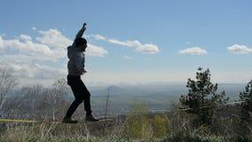 Een mens die een hoed en een baard dragen loopt slackline tijdens de wind tegen de achtergrond van de bergen van de Kaukasus van stock footage