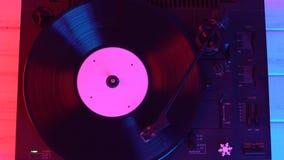 Een mens die een retro platenspeler beginnen, bepaalt de naald en luistert aan muziek stock footage