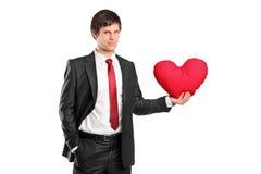 Een mens die een rood hart-vormig hoofdkussen houdt Royalty-vrije Stock Foto's