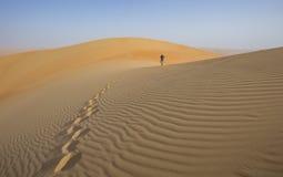 Een mens die in een woestijn lopen Royalty-vrije Stock Foto's