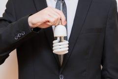 Een mens die een energy-saving gloeilamp houden Royalty-vrije Stock Fotografie