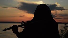 Een mens die een fluit spelen bij zonsondergang stock footage