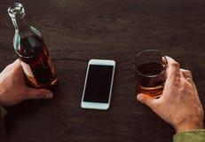 Een mens die een glas whisky en een fles alcohol, op de lijst houden is een mobiele telefoon stock afbeeldingen