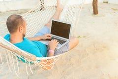 Een mens die in een hangmat liggen die de oceaan overzien De kerel met royalty-vrije stock fotografie