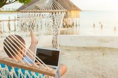 Een mens die in een hangmat liggen die de oceaan overzien De kerel met stock foto