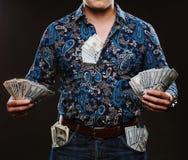 Een mens die heel wat geld houden Bankbiljetten van 100 dollars in verschillende zakken, het concept corruptie Stock Foto's