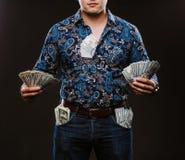 Een mens die heel wat geld houden Bankbiljetten van 100 dollars in verschillende zakken, het concept corruptie Stock Afbeelding