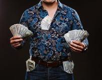 Een mens die heel wat geld houden Bankbiljetten van 100 dollars in verschillende zakken, het concept corruptie Stock Foto