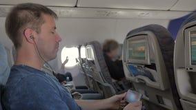 Een mens die in hoofdtelefoons op een video letten, die aan muziek op zijn mobiele telefoon luisteren, die op het vliegtuig zitte stock video