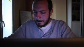Een mens die/iets op het Web bestuderen zoeken bij de studieruimte Hij schrijft iets op toetsenbord en hij kijkt vermoeid stock videobeelden
